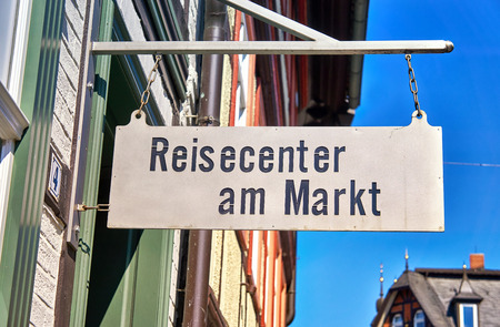 Old sign with the text Travel Agency. In German Reisecenter am Markt.