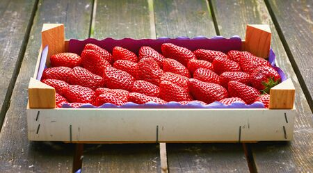 Wooden box with fresh red strawberries and old wooden background.