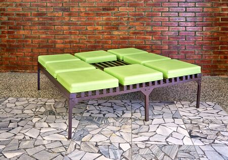 Modern green metal and leather bench in front of a brick wall.