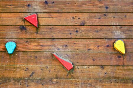 Wooden climbing wall with colorful handles as a background.