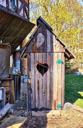 Wooden ecological compost toilet with a heart shape in the door.