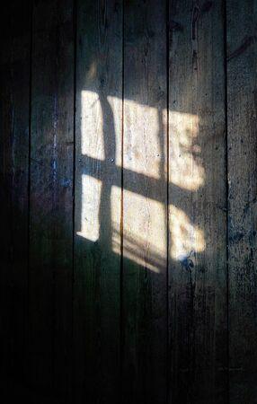 Light shines through a window on the wooden wall background. 版權商用圖片