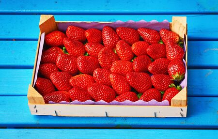 Fresh red strawberry with wooden box and blue wood background.