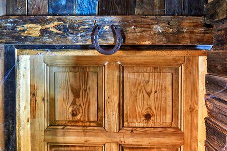Metal horseshoe nailed over an old door.