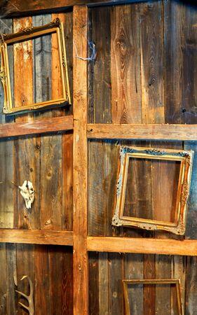 Old picture frames hang on wooden vintage background.