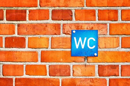 Old Red brick wall with blue toilet sign.