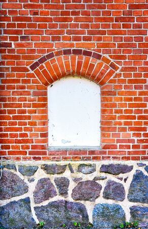 White window with space for text on a brick and natural stone wall.