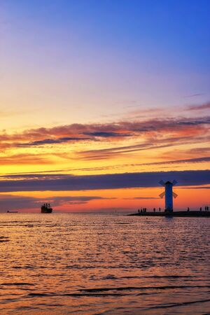Tourist boat in the Baltic Sea with beautiful sunset over a windmill shaped lighthouse in Swinoujscie. Swinoujscie, Poland