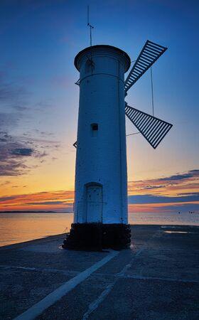 Lighthouse in sunset in Swinoujscie on the Baltic Sea. Swinoujscie, Poland Фото со стока