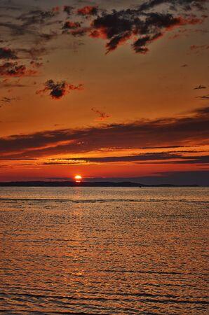 Orange sunset with beautiful sky on the Baltic Sea beach.