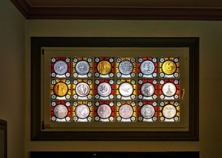 Historic German glass coins on a window.