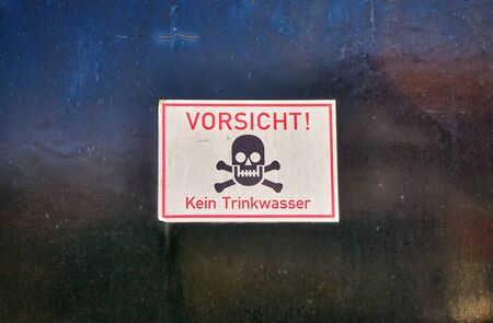 Skull on a warning sign. Caution no drinking water in German letters.