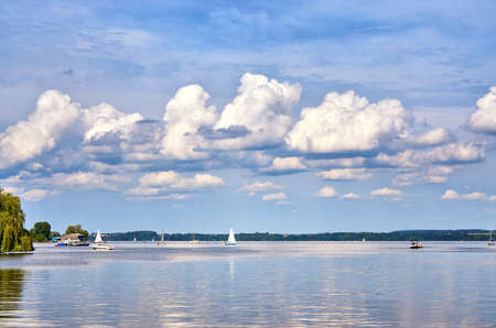 Sky with gigantic clouds over a lake with sailing boats and motor boats. 版權商用圖片