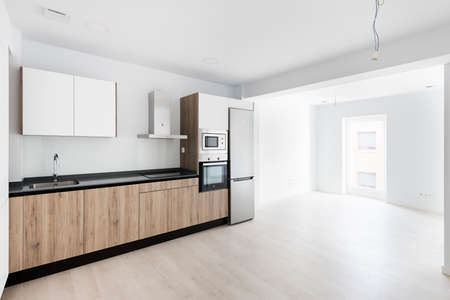 Counters with sink and located in spacious light kitchen in contemporary apartment 版權商用圖片