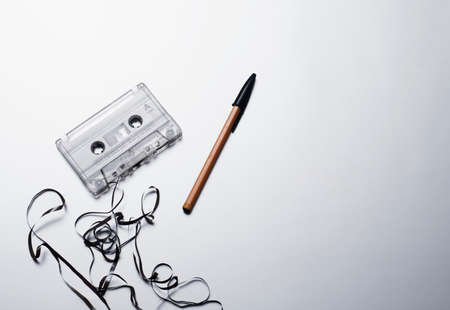 From above of retro plastic audio cassette with tangled tape arranged near pen on white background