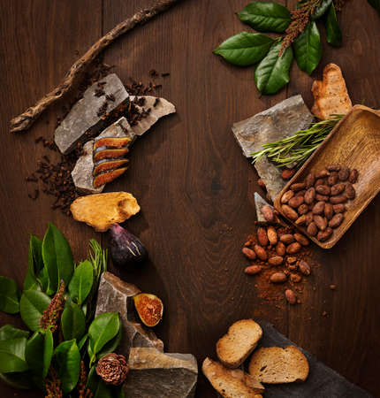 Top view of assorted exotic fruits and green flowers placed on green leaves on dark wooden tabletop