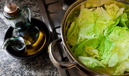 Steamed pot with cabbage cooking and an oil pot with Mediterranean olive oil in a home kitchen