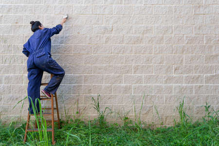 female painter dressed in work overalls painting with a brush to paint the wall. space on the right to label.
