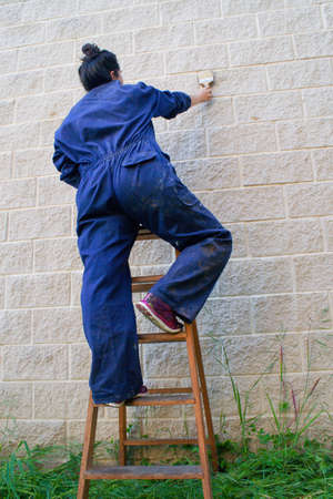 painting woman dressed in work overalls climbing an old wooden ladder painting with a paint brush. low angle shot.