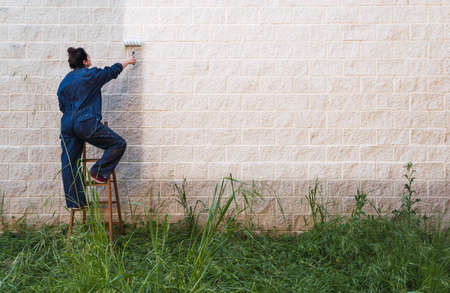 female painter painting the wall with a paint roller on top of an old wooden ladder. Leave a white mark to label.