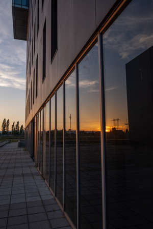 sunset reflected in a glass window of a brown business office building Imagens