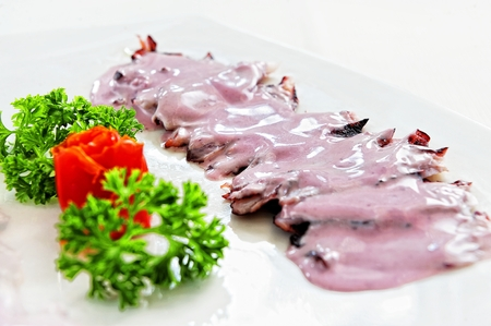 Pulpo al Olivo, traditional dish of Peruvian cuisine made from an olive sauce, on a white background.