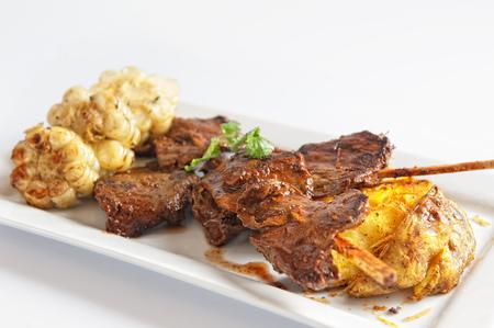 anticuchos, cuisine péruvienne, brochette de viande de coeur de boeuf grillée avec pomme de terre bouillie et maïs blanc