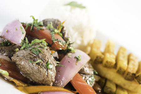 Peruvian food lomo saltado :A salted beef with tomatoes, onion, fried potatoes and rice. Stock Photo