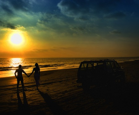 Honeymoon romantic couple in love walking on the beach on orange sunset background, happy young couple embracing enjoying ocean sunset during travel holidays vacation. Banque d'images