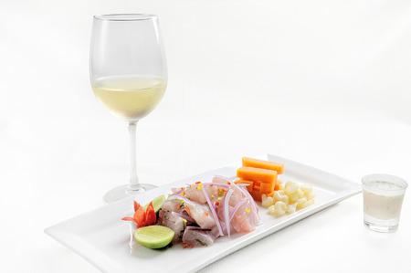 Ceviche, dish symbol of Peruvian gastronomy. On a white background. Accompanied by a glass of white wine and Leche de Tigre. Standard-Bild