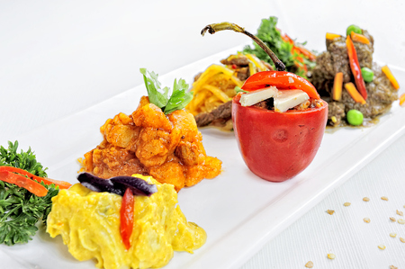 Peruvian food: Rocoto relleno , a pepper stuffed with flour and cheese. accompanied by Carapulcra, Olluquitos, Seco de Carne and Aji de Gallina, on a white background surrounded by Ajies.