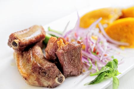 Traditional Peruvian Meal Called Chicharron de Panceta de Cerdo Served in a Restaurant. Accompanied with a Tamal.