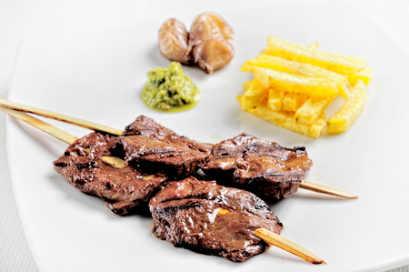 Anticuchos, Peruvian cuisine, grilled skewered beef heart meat with boiled potato and white corn.