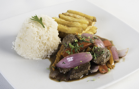 Peruvian food lomo saltado :A salted beef with tomatoes, onion, fried potatoes and rice. On a white background.