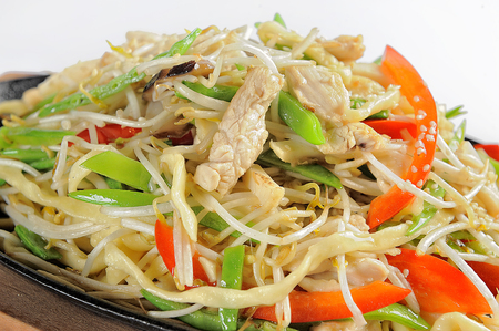 chinese stir-fried noodles with chicken. On a white background. Stock Photo