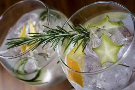 Low angle close up of ice cold modern gourmet craft cocktail of gin and tonic soda garnished by lemon slice and rosemary sprig sprinkled by juniper berries on bar with blurry restaurant bar background. Colorfull