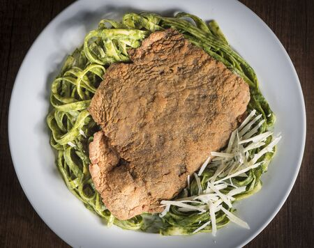 Pasta with basil pesto sauce on plate, closeup. green noodles with breaded