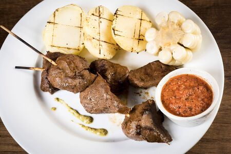 anticuchos, Peruvian cuisine, grilled skewered beef heart meat with boiled potato and white corn. Peru Zdjęcie Seryjne