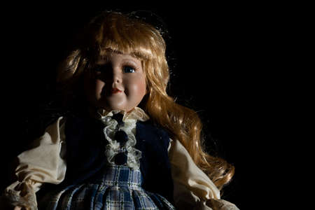 Creepy porcelain doll in a black background