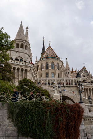 St. Matthias Church in Budapest, Hungary. Cloudy sky. Green trees.