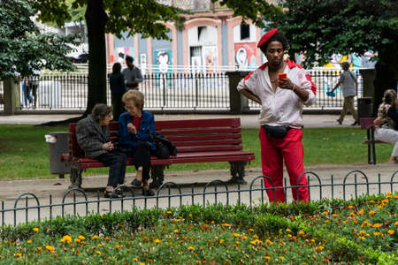 Artist guy dressed in red and white using the smartphone. Two ladies talking in the background. City of Porto Editorial