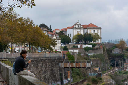 Two man somoking, sitting on the edge of a wall, while sightseeing. Buildings and trees on the background. Porto