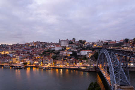 Beutiful Porto view, with Dom Luís Bridge and metro. Sunset, blue sky and clouds. Boats on the river. Editorial