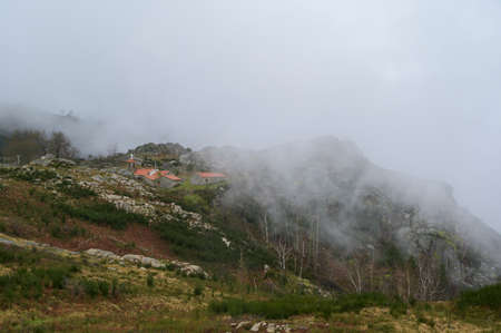 Small houses with orange roofs in the middle of hills. Green grass contrasting with yellow grass. Foggy day. Freita mountain range. Portugal