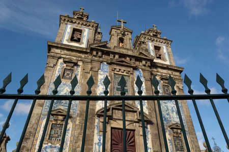 Santo Ildefonso church with arrow fence. . Blue relegious tiles. Cloudy sky. Porto, Portugal