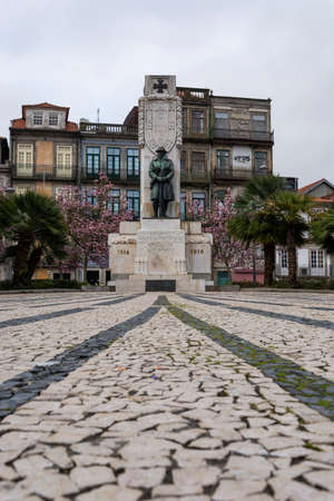 Memorial to the people from Porto that died in the first great war. Iron soldier statue. Trees in flower and colorful buildings. Porto, Portugal Editorial