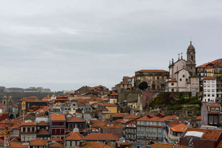 Porto, Portugal - 11/27/2019: Porto, Portugal. View to Porto's downtown from the cathedral view point. Church on the top of the hill. Portuguese traditional houses with orange roofs. Editorial