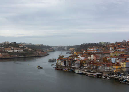 Porto, Portugal - 11/27/2019: Porto, Portugal. View to the city of Porto and Douro river. Douro river with boats. Ribeira e Vila Nova de Gaia. Cloudy sky. Editorial