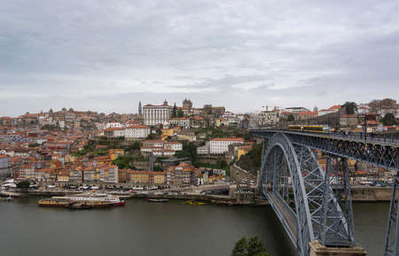 Porto, Portugal - 11/27/2019: Porto view, with Dom Luís Bridge and metro. Sunset, cloudy sky. Boats on the river.