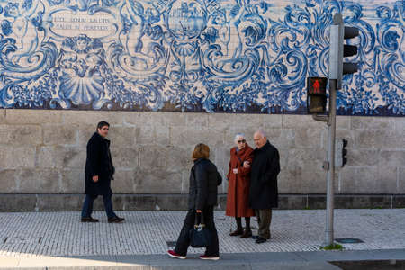 Porto, Portugal - 11/27/2019: People walking in the sidewalk, preparing to cross the street. Green traffic light. Traditional portuguese tiles in the background.